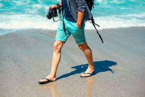 Man walking at the beach with camera