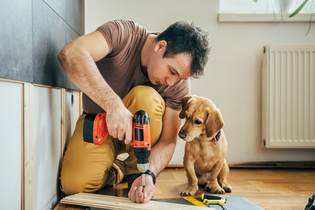man constructing something in house while dog watches